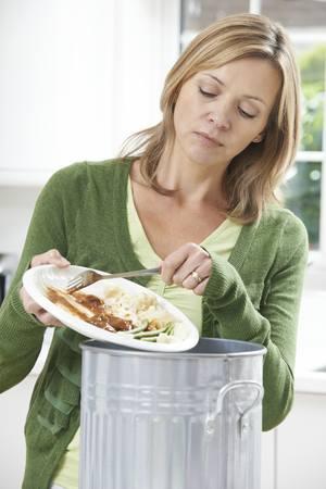 Woman Scraping Food Leftovers Into Bin